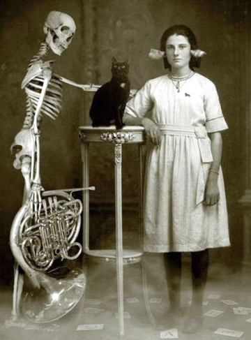 Girl with skeleton, french horn and black cat