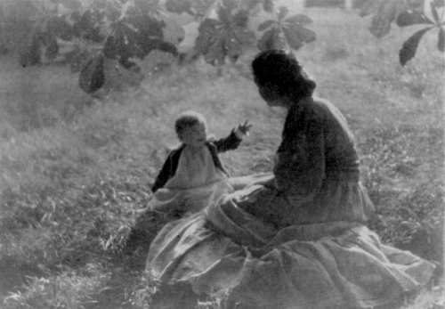 A photo of a young mother and child sitting on the lawn